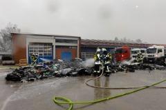 Einsatzkräfte löschen den brennenden Plastikabfall von mehreren Seiten ab.