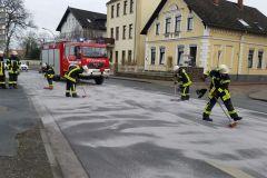 Einsatzkräfte der Feuerwehr streuen die Dieselspur mit Bindemittel ab.