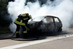 Ein Feuerwehrmann ist mit dem Ablöschen des PKW beschäftigt.