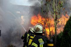 Ein Trupp unter Atemschutz kühlt die Fassade des Reihenhauses.