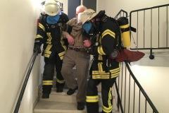 Eine Person wird über das Treppenhaus gerettet. Um realistische Sichtbedingungen durch Rauch zu simulieren, wurden die Masken der Atemschutzgeräteträger mit Folie abgedeckt.