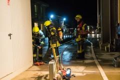 Ein Atemschutztrupp bereitet sich auf die bevorstehende Menschenrettung aus dem verrauchten Gebäude vor.