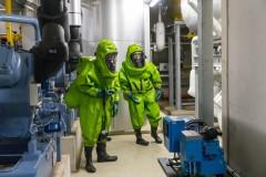 Feuerwehrleute in Chemikalienschutzanzügen führen im Technikraum Messungen durch.