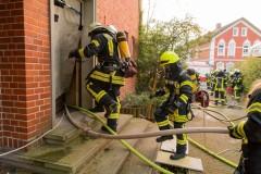 Einsatzkräfte ausgerüstet mit Atemschutz gehen in das komplett verrauchte Gebäude vor.
