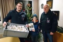 Der neunjährige Quentin Sander überreichte Ortsbrandmeister Jürgen Barkfrede und seinem Stellvertreter Tobias Burmeister Kekse für die Feuerwehr.