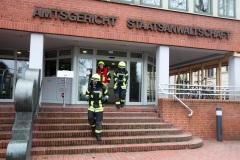 Ein Trupp unter Atemschutz verlässt das Gerichtsgebäude.