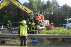 Feuerwehr und Rettungsdienst befreien den eingeklemmten Baggerfahrer.
