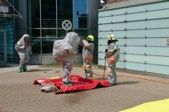 Einsatzkräfte unter Chemikalienschutzanzug werden nach ihrem Einsatz dekontaminiert.