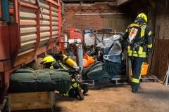 Feuerwehrleute unter Atemschutz suchen nach einer vermissten Person.