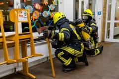 Einsatzkräfte unter Atemschutz durchsuchen das Gebäude nach vermissten Personen.