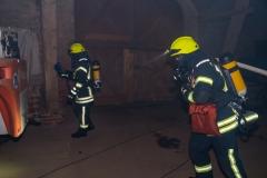 Feuerwehrleute unter Atemschutz durchsuchen die Scheune nach den vermissten Technikern.