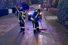 Einsatzkräfte der Feuerwehr bringen Ölbindemittel auf die Straße aus, um das Öl zu binden.