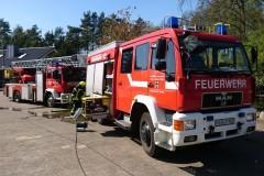 Einsatzfahrzeuge der Feuerwehr vor dem Brandobjekt.