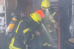 Einsatzkräfte unter Atemschutz retten eine Person aus einem verrauchten Nebengebäude.