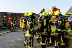 Einsatzkräfte unter Atemschutz bereiten sich auf ihren Einsatz zur Menschenrettung aus dem vollkommen verqualmten Büroanbau vor.