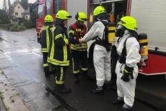 Einsatzkräfte rüsten sich mit Schutzanzügen und Atemschutz aus.