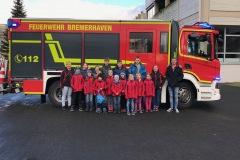 Die Kinder- und Jugendfeuerwehr Eitze vor einem Hilfeleistungslöschgruppenfahrzeug auf der Berufsfeuerwehrwache Bremerhaven.