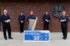 Vertreter der Ortsfeuerwehren empfangen aus der Materialspende gefertigte Mund-Nasen-Schutze. Stadtbrandmeister Peter Schmidt (rechts) dankt stellvertretend Markus Grefe (Mitte) von der Firma Statex.