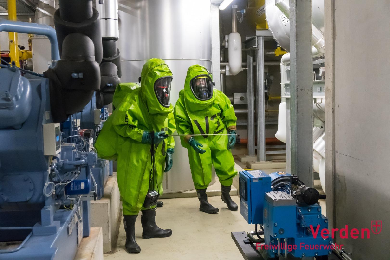 Einsatzkräfte in Chemikalienschutzanzügen erkunden eine Einsatzstelle.