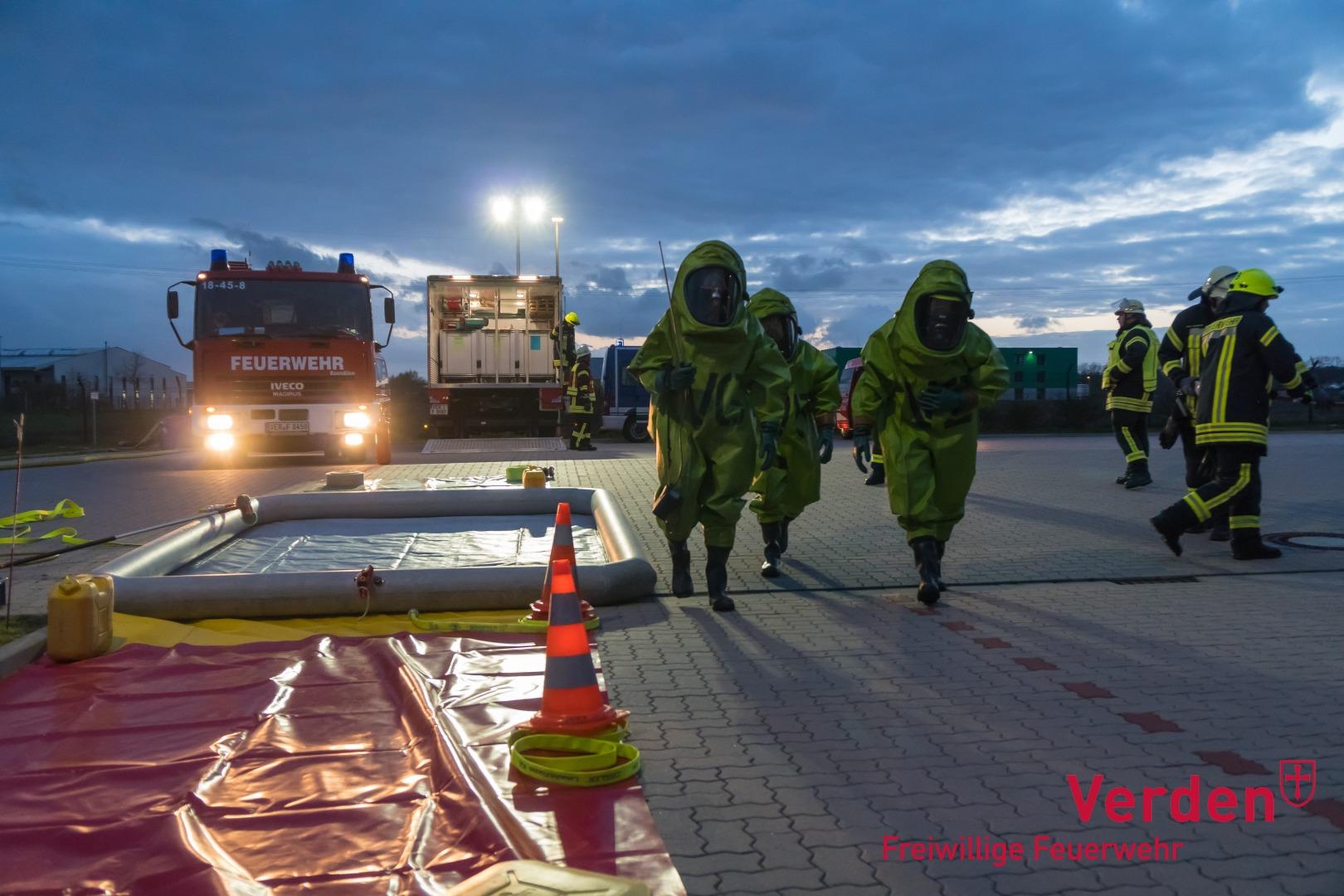 Einsatzkräfte in Chemikalienschutzanzügen neben der Dekontaminationsstrecke.